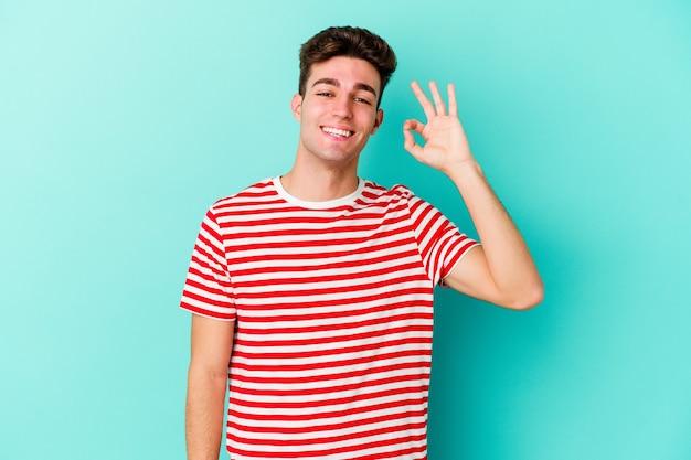 Il giovane uomo caucasico isolato sulla parete blu strizza l'occhio e tiene un gesto giusto con la mano