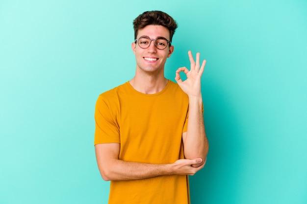 Il giovane uomo caucasico isolato sulla parete blu strizza l'occhio e tiene un gesto giusto con la mano.
