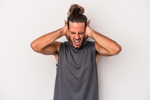Giovane uomo caucasico isolato su sfondo grigio che copre le orecchie con le mani cercando di non sentire un suono troppo forte.