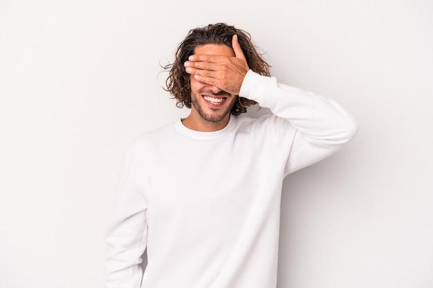 Il giovane uomo caucasico isolato su sfondo grigio copre gli occhi con le mani, sorride ampiamente in attesa di una sorpresa.