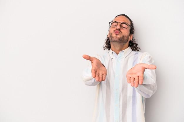 Giovane uomo caucasico isolato su sfondo grigio piegando le labbra e tenendo i palmi delle mani per inviare un bacio d'aria.