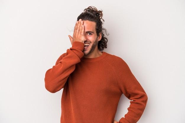 Giovane uomo caucasico isolato su sfondo grigio divertirsi coprendo metà del viso con il palmo.