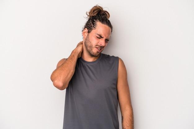 Giovane uomo caucasico isolato su sfondo grigio con dolore al collo dovuto allo stress, massaggiandolo e toccandolo con la mano.
