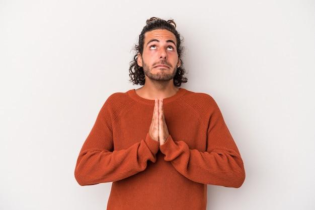 Il giovane uomo caucasico isolato su sfondo grigio tenendosi per mano in preghiera vicino alla bocca, si sente sicuro.