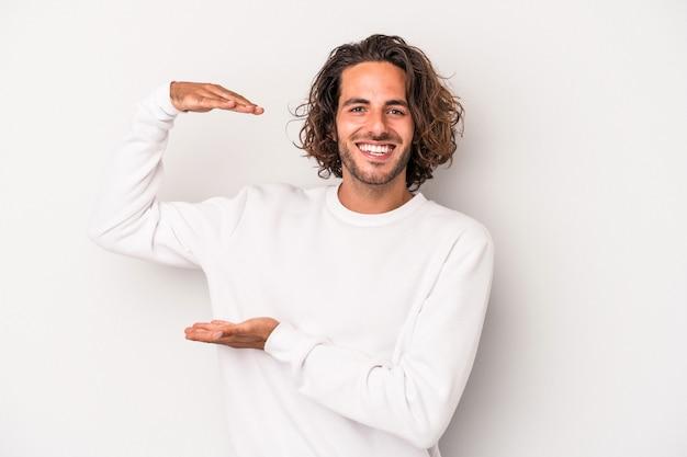 Giovane uomo caucasico isolato su sfondo grigio che tiene qualcosa di piccolo con l'indice, sorridente e fiducioso.
