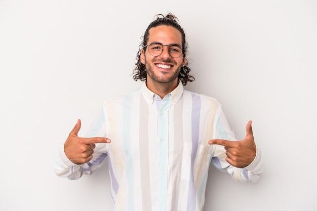 Il giovane uomo caucasico isolato su sfondo grigio punta verso il basso con le dita, sensazione positiva.