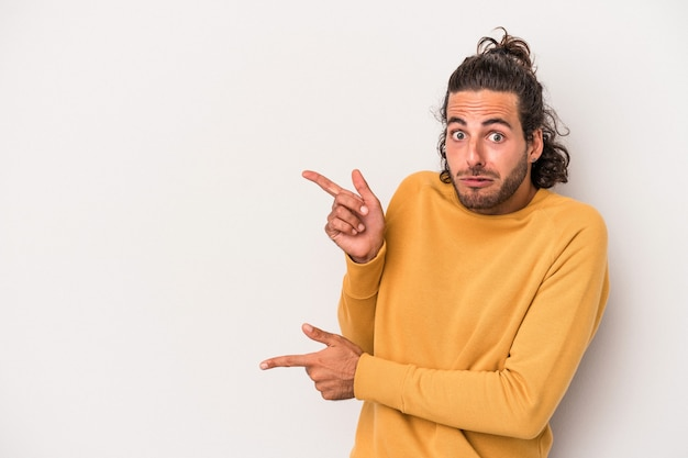 Giovane uomo caucasico isolato su sfondo grigio scioccato indicando con il dito indice uno spazio di copia.