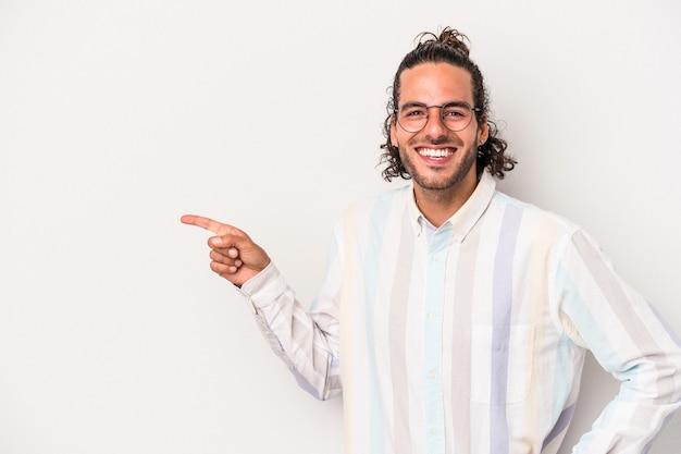 Giovane uomo caucasico isolato su sfondo grigio sorridente allegramente puntando con l'indice lontano.