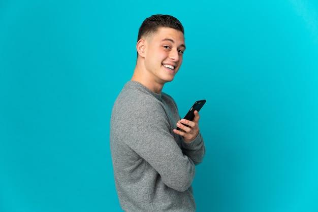 Giovane uomo caucasico isolato in possesso di un telefono cellulare e con le braccia incrociate