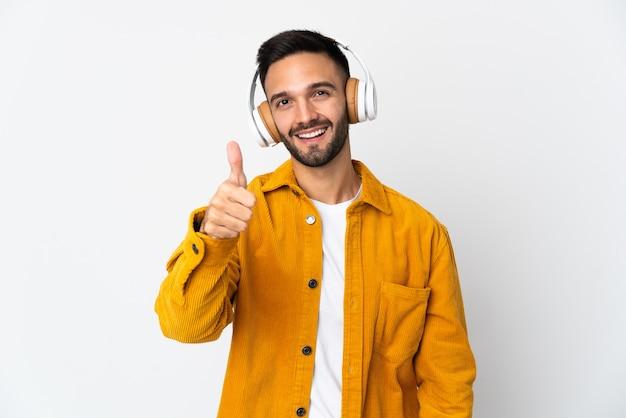 Il giovane uomo caucasico ha isolato la musica d'ascolto e con il pollice in su