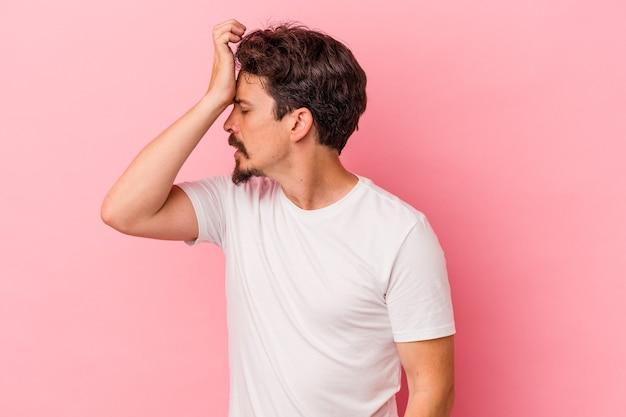 Giovane uomo caucasico isolato su sfondo rosa dimenticando qualcosa, schiaffeggiando la fronte con il palmo e chiudendo gli occhi.