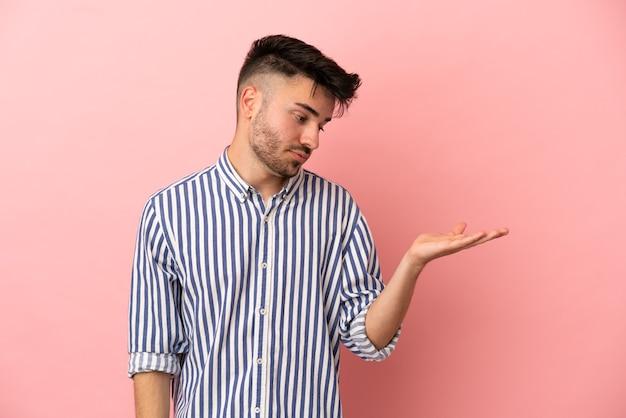 Giovane uomo caucasico isolato su sfondo rosa tenendo copyspace con dubbi
