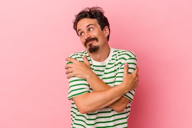 Il giovane uomo caucasico isolato sugli abbracci rosa del fondo, sorride spensierato e felice.
