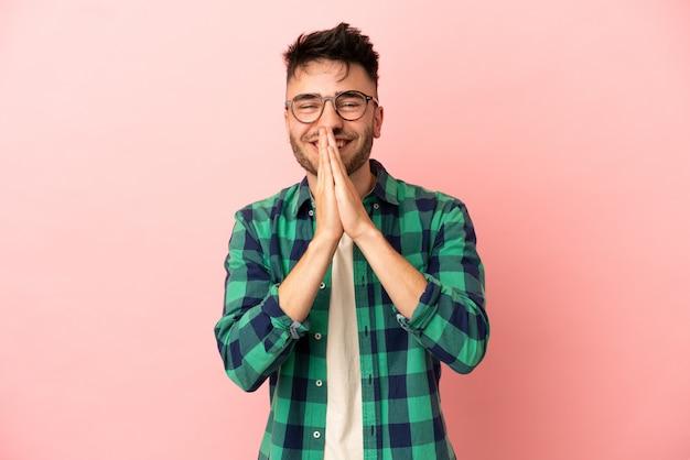 Il giovane uomo caucasico isolato su sfondo rosa tiene insieme il palmo. la persona chiede qualcosa