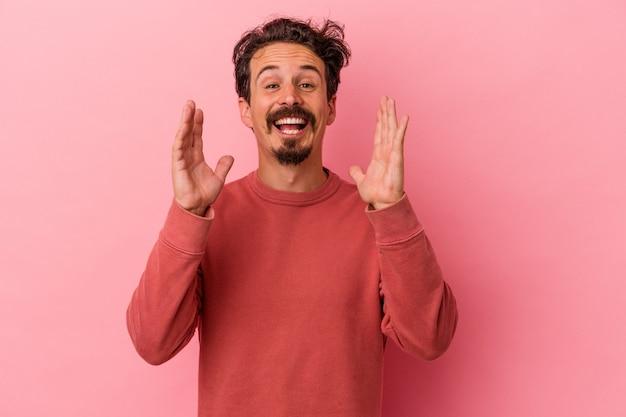 Il giovane uomo caucasico isolato su sfondo rosa ride forte tenendo la mano sul petto.