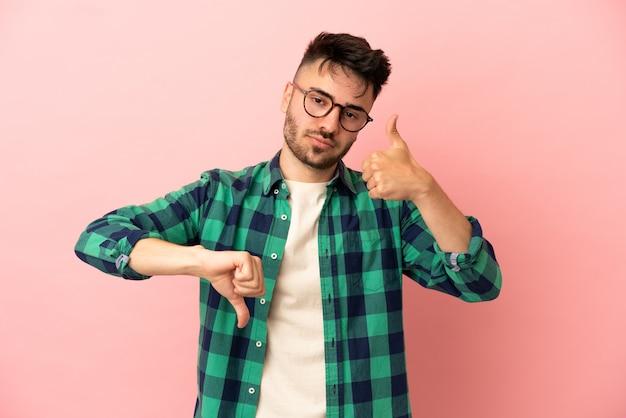 Giovane uomo caucasico isolato su sfondo rosa facendo segno buono-cattivo. indeciso tra si o no