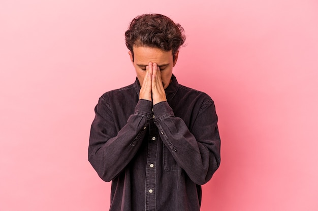 Giovane uomo caucasico isolato su sfondo rosa che prega, mostra devozione, persona religiosa in cerca di ispirazione divina.