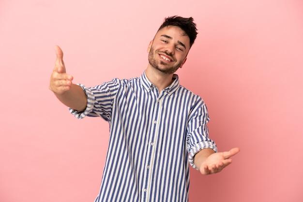 Giovane uomo caucasico isolato su sfondo rosa che presenta e invita a venire con la mano