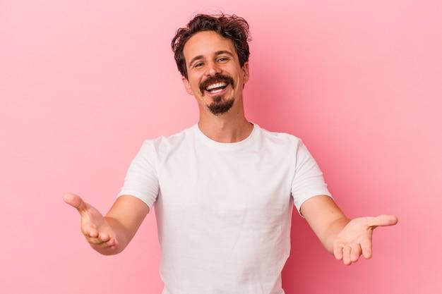 Giovane uomo caucasico isolato su sfondo rosa che mostra un'espressione di benvenuto.