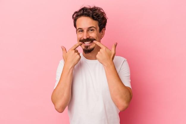 Il giovane uomo caucasico isolato su sfondo rosa sorride, puntando il dito alla bocca.
