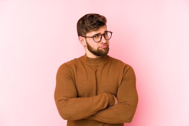 Giovane uomo caucasico isolato su sfondo rosa infelice guardando a porte chiuse con espressione sarcastica.