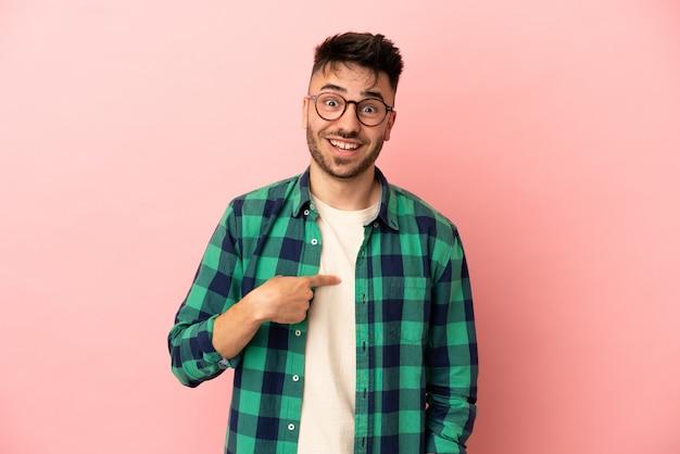 Giovane uomo caucasico isolato su sfondo rosa con espressione facciale a sorpresa