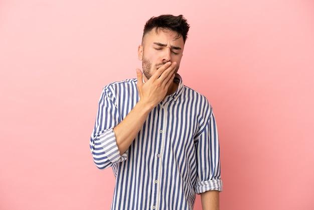 Giovane uomo caucasico isolato su sfondo rosa che sbadiglia e copre la bocca spalancata con la mano