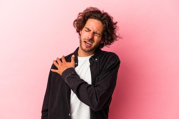 Giovane uomo caucasico isolato su bakcground rosa che ha un dolore alla spalla.