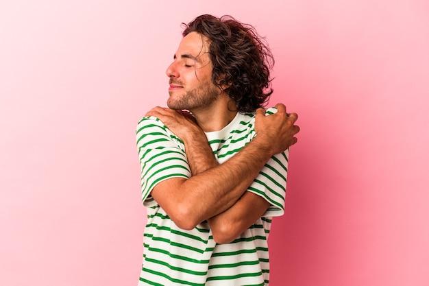 Giovane uomo caucasico isolato su abbracci rosa bakcground, sorridente spensierato e felice.