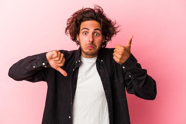 Giovane uomo caucasico isolato su sfondo rosa che mostra pollice in alto e pollice in basso, difficile scegliere il concetto