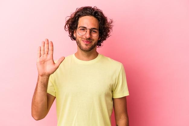 Giovane uomo caucasico isolato su bakcground rosa sorridente allegro che mostra il numero cinque con le dita.