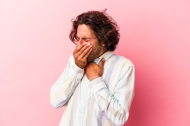 Il giovane uomo caucasico isolato su sfondo rosa soffre di dolore alla gola a causa di un virus o di un'infezione.