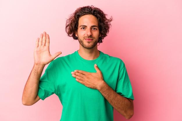 Giovane uomo caucasico isolato su bakcground rosa prestando giuramento, mettendo la mano sul petto.