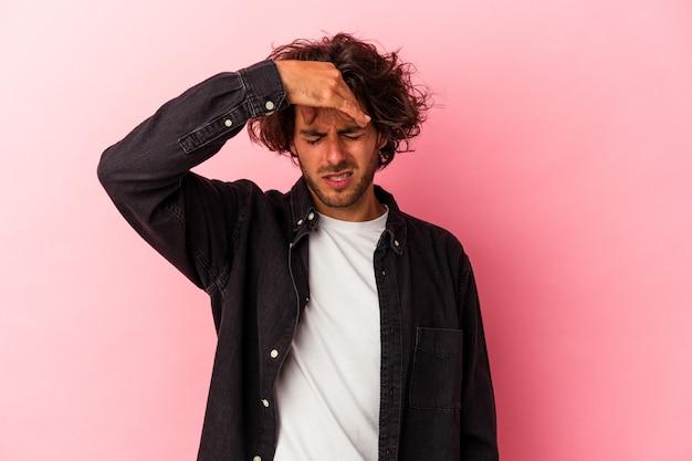 Giovane uomo caucasico isolato su bakcground rosa toccando le tempie e avendo mal di testa.