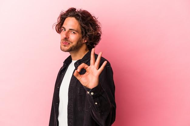 Il giovane uomo caucasico isolato su bakcground rosa strizza l'occhio e tiene un gesto ok con la mano.
