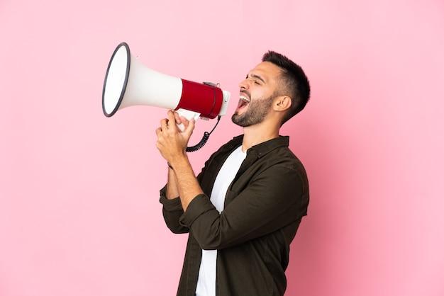 Giovane uomo caucasico isolato sulla parete rosa che grida tramite un megafono per annunciare qualcosa in posizione laterale
