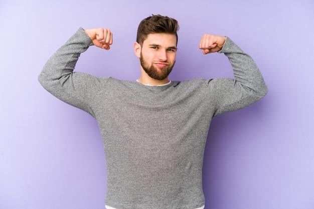Giovane uomo caucasico isolato su sfondo viola che mostra il gesto di forza con le braccia, simbolo del potere femminile
