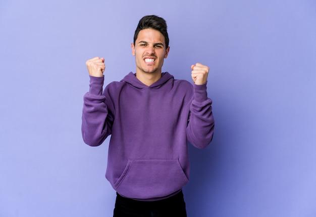 Giovane uomo caucasico isolato su sfondo viola sconvolto urlando con le mani tese.
