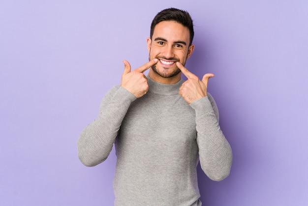 Giovane uomo caucasico isolato su sorrisi viola, puntando le dita alla bocca.