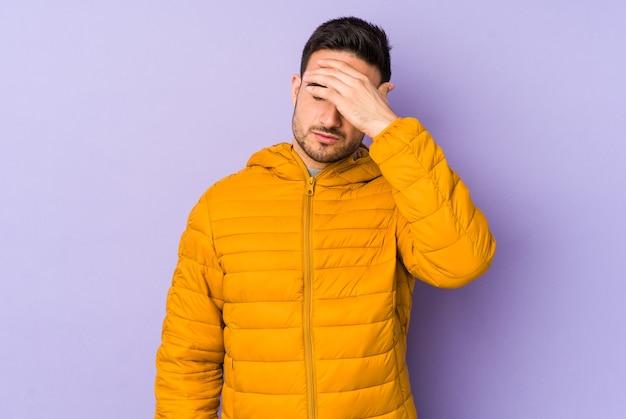 Giovane uomo caucasico isolato su viola toccando le tempie e avendo mal di testa.