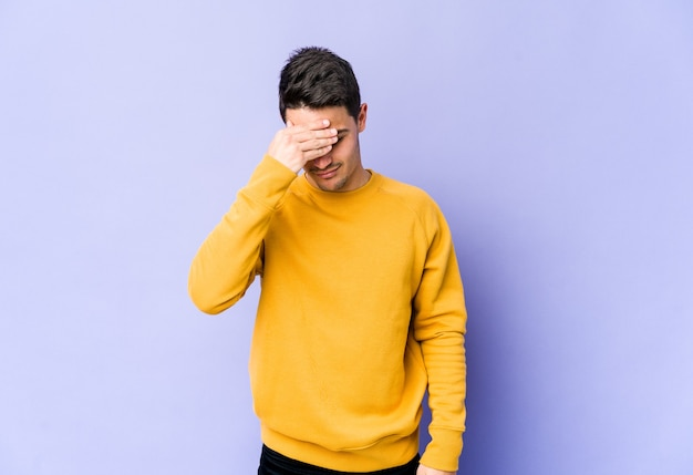 Giovane uomo caucasico isolato sulla parete viola con mal di testa, toccando la parte anteriore del viso.