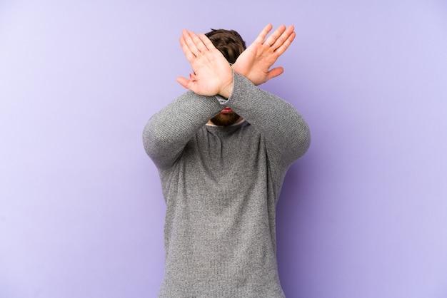 Giovane uomo caucasico isolato sulla parete viola mantenendo due braccia incrociate, concetto di negazione.