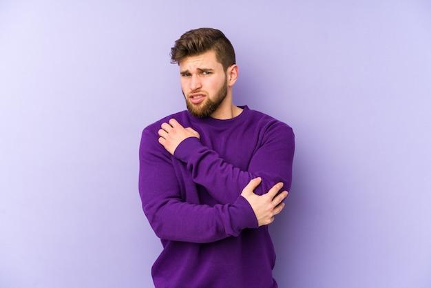 Giovane uomo caucasico isolato sul muro viola massaggiando il gomito, che soffre dopo un brutto movimento.