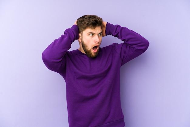 Giovane uomo caucasico isolato sulla parete viola che grida, molto eccitato, appassionato, soddisfatto di qualcosa.