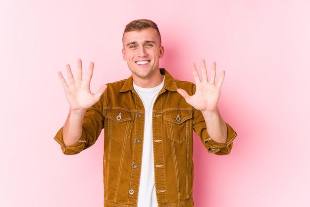Giovane uomo caucasico isolato mostrando numero dieci con le mani.
