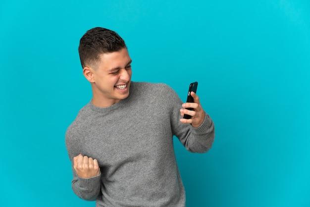 Giovane uomo caucasico isolato utilizzando il telefono cellulare e facendo il gesto di vittoria