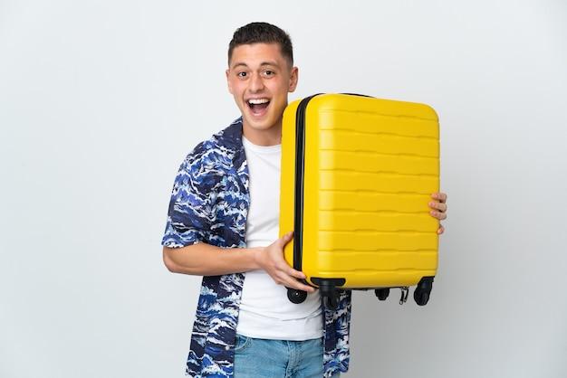 Giovane uomo caucasico isolato in vacanza con la valigia di viaggio e sorpreso
