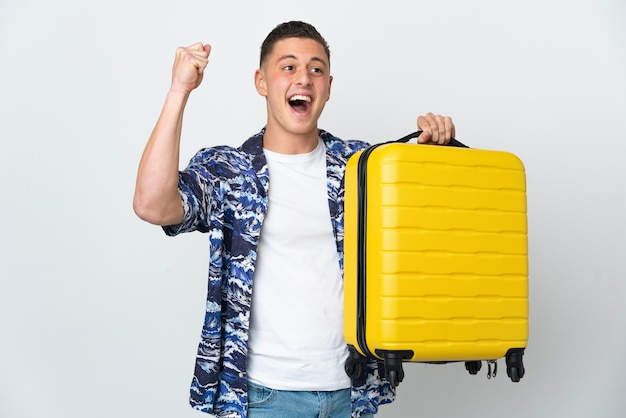 Giovane uomo caucasico isolato in vacanza con la valigia da viaggio