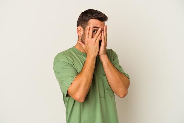 Giovane uomo caucasico isolato su sfondo bianco sbattere le palpebre attraverso le dita spaventato e nervoso.