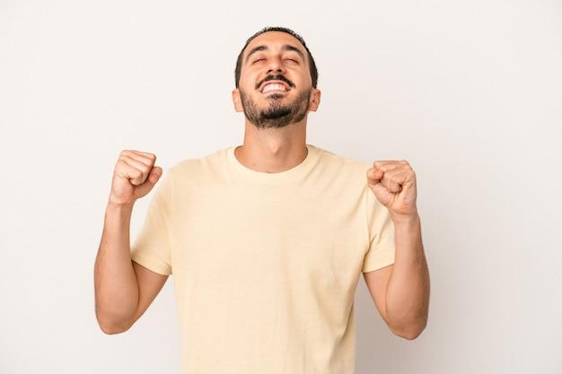 Giovane uomo caucasico isolato su sfondo bianco che celebra una vittoria, passione ed entusiasmo, espressione felice.